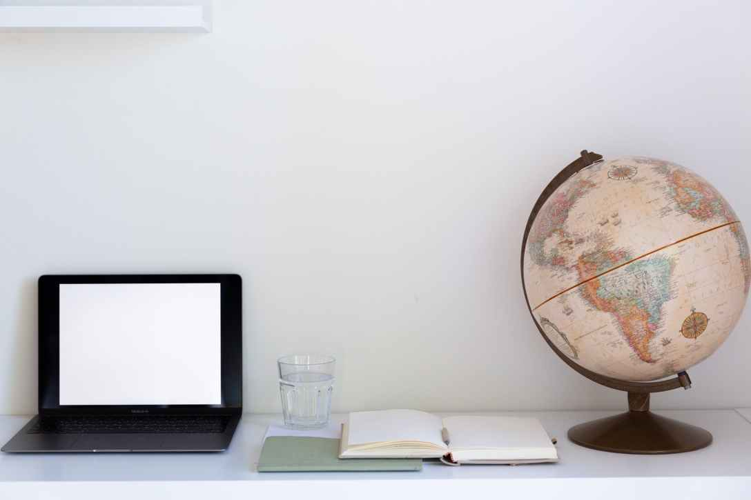 minimalistic workplace with blank screen of laptop opened planner and retro globe